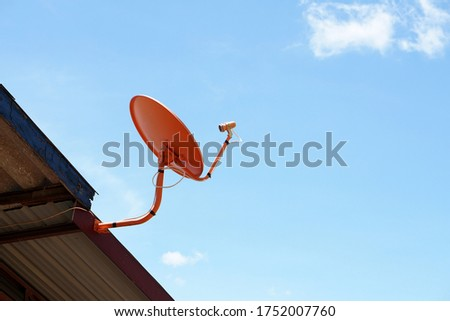 Orange satellite dish dish for receiving TV signals Attached to the roof of the house In order to be in a high place and open to receive signals well #1752007760