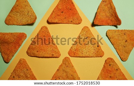 Geometrically organised corn chips on a bright background. Food knolling picture of corn chips.