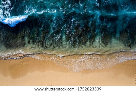 Abstract drone view taken directly from above of some tidal waves breaking along the shoreline of a beach in Bali Indonesia. Royalty-Free Stock Photo #1752023339