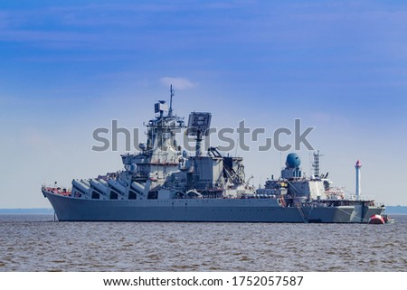 "A warship is sailing in the sea. Missile cruiser against the sky. Weapons Russian warship view from afar. Naval forces. Russian weapons. Kreser ""Marshal Ustinov"". Ship with a lot of weapons on board #1752057587"