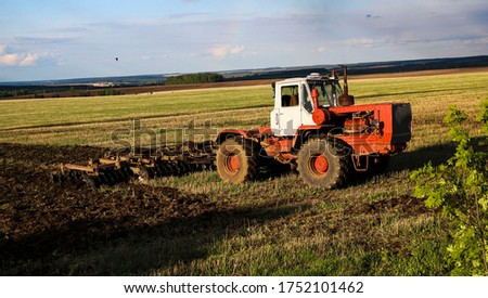 the tractor plows and harrows the land in a large field on a sunny spring day. preparing the soil for planting crops, plowing the soil with a tractor with a disk plow. #1752101462