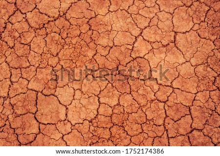 Nature background of cracked dry lands. Natural texture of soil with cracks. Broken clay surface of barren dryland wasteland close-up. Full frame to terrain with arid climate. Lifeless desert on earth Royalty-Free Stock Photo #1752174386