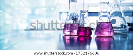 purple glass flask in blue research chemistry science banner laboratory background  Royalty-Free Stock Photo #1752176606