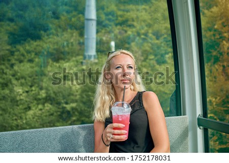 girl with a cocktail in the cabin of the ski lift