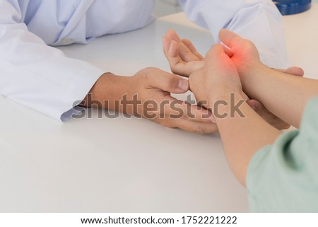 Asian orthopaedic doctor doing physical examination in the patient with wrist pain and numbness at the clinic. Selective focus at right hand with red hi light. Medical concept