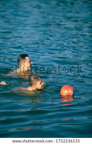 father with kid having fun in water swimming together