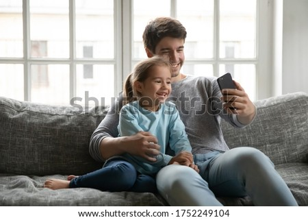 Smiling young Caucasian father and small preschooler daughter sit on sofa at home make self-portrait picture on cellphone, happy dad and little girl child take selfie on smartphone gadget together