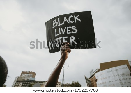 "Black lives matter movement protesting in Milan, claiming for antiracism and equal human rights holding ""Black lives matter"" picket sign #1752257708"