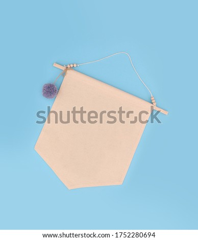 A blank fabric banner mock up with a wooden stick, wooden beads and blue pompom, top view empty fabric banner on blue background