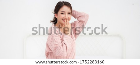 Smiling of cheerful beautiful pretty asian woman clean fresh healthy white skin posing in warm knitted pink clothes.Girl felling relaxing and enjoy time on the bed at home.asia beauty