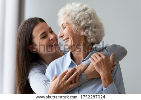 Loving cheerful grown up daughter hugs elderly mother from behind, multi generational relatives beautiful women enjoy time together laughing having fun, love care understanding concept, close up image #1752287024