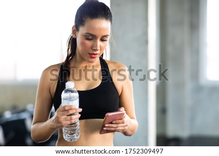 Active woman athlete taking rest and use smartphone after exercising at gym. Fitness Healthy lifestye and workout at gym concept.