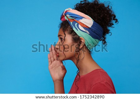 Side view of young attractive dark haired curly female with gathered hair keeping raised palm near her mouth while going to tell something secret, isolated over blue background #1752342890