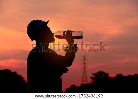 Silhouette engineer drinking fresh water when he feel thirsty after finish checking and inspection railway with twilight sky background.