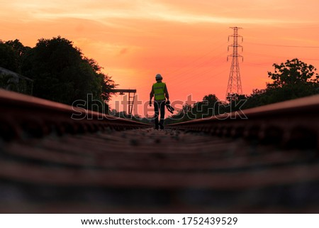 The engineer under inspection and checking construction railroad station .Engineer wearing safety uniform and safety helmet work, holding camera to take photo on work. #1752439529