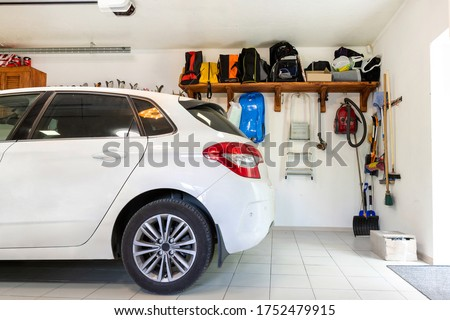 Home suburban car garage interior with wooden shelf , tools and equipment stuff storage warehouse on white wall indoors. Vehicle parked at house parking background #1752479915