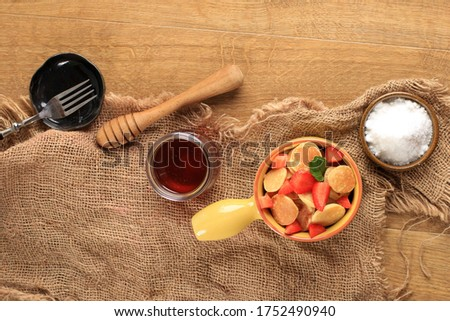 Top View Yellow Bowl with Handle  Full of Tiny Pancake or Popular as Cereal Pancake, Viral Snack During Quarantine in 2020. Picture with Strawberry and Mint as Garnish, Copy Space