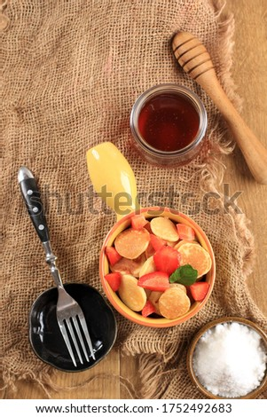 Top View Yellow Bowl with Handle  Full of Tiny Pancake or Popular as Cereal Pancake, Viral Snack During Quarantine in 2020. Served Above Jute Brown Background,Copy Space, Vertical Picture