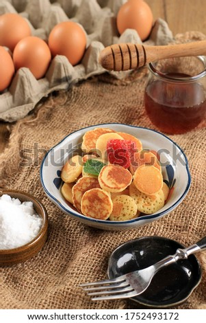 Close Up Bowl Full of Tiny Pancake or Popular as Cereal Pancake, Popular Viral Snack During Quarantine in 2020. Served Above Jute Brown Background with Fork, Vertical Version Picture