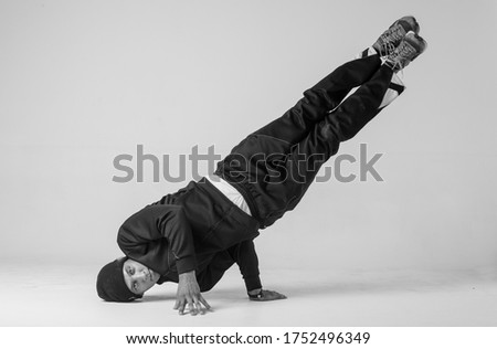 A man hip hop dancer or bboy freezes in one pose on a white background. Bboy doing stylish stunts. #1752496349