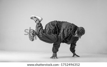 A man hip hop dancer or bboy freezes in one pose on a white background. Bboy doing stylish stunts. #1752496352