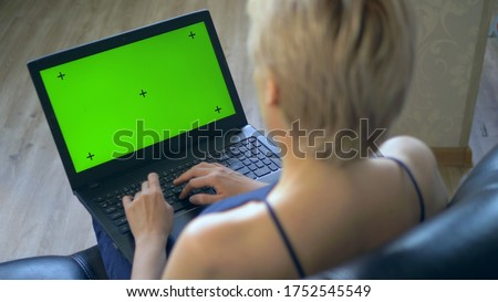 chroma key on laptop screen. look over your shoulder. woman uses laptop at home.
