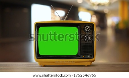 Yellow orange color old vintage retro Television on wood table with green screen .