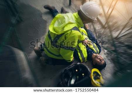 Construction worker accident, Accidents at work, Builder accident fall scaffolding to the floor, Safety team help employee accident, Basic first aid training for support accident in site work. #1752550484