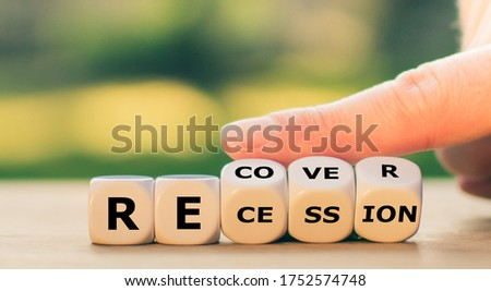 "Symbol for the economy after the corona virus. Hand turns dice and changes the word ""recession"" to ""recover"". Royalty-Free Stock Photo #1752574748"