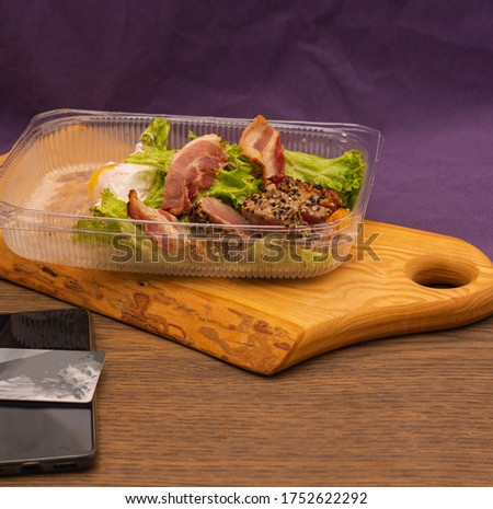 Salad with lettuce, tuna, bacon and egg in disposable plastic box. food delivered from a restaurant #1752622292
