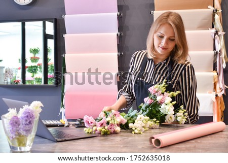 flower business. The florist makes a bouquet. The seller in floristic salon. Delivery of bouquets. #1752635018