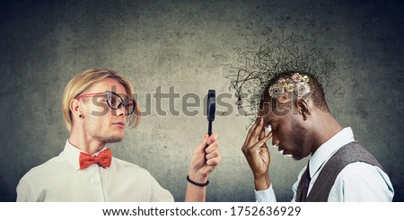 Curious young man looking through a magnifying glass at a thoughtful man with a mess in his head Royalty-Free Stock Photo #1752636929