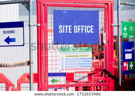 First aid site office sign on construction building site door entrance fence