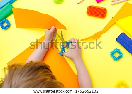 Child cutting colored orange paper with scissors  on a table for some craftwork