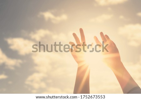 Woman hands reaches for the sky and closes the sun, the sun's rays pass through the hand Royalty-Free Stock Photo #1752673553