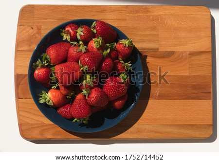 Plate of ripe strawberries on a wooden background. Fresh juicy summer red with green strawberries on a dark blue plate. Summer shopping concept, vitamins stock, proper nutrition, veganism, harvest