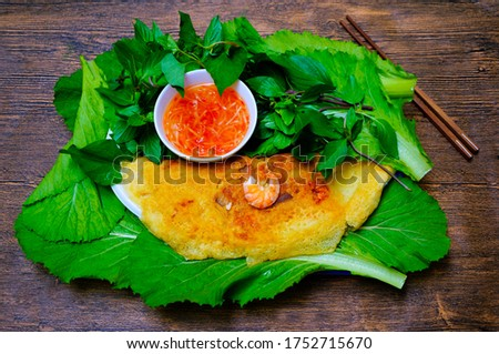 Vietnamese Savory Fried Pancake (aka Vietnamese Sizzling Rice Fried Pancake). Served with fresh vegetables, herbs, and fish sauce.  Vietnamese cuisine. (Vietnamese name of this crepe : Bánh Xèo). #1752715670