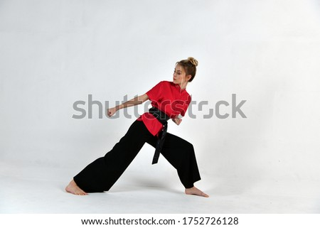 beautiful girl in black and red does exercises for mastery of martial arts Royalty-Free Stock Photo #1752726128