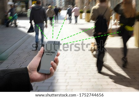Smart phone with Corona Warn App, a contact tracking or tracing application against Covid 19 pandemic is connecting other phones from moving people in the city to analyze the risk of infection Royalty-Free Stock Photo #1752744656