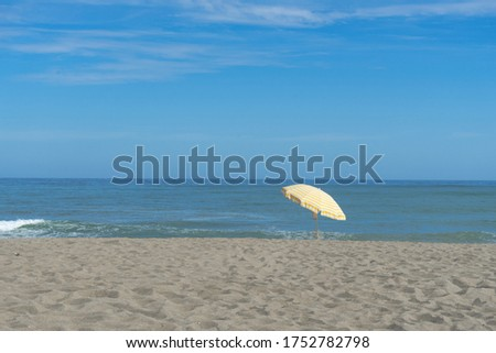 A quiet beach with a yellow parasol on a sunny day. #1752782798