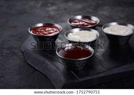 Set of sauces - ketchup, tartar sauce, bbq sauce, spicy sauce, cesar sauce on dark wood background. Closeup #1752790751