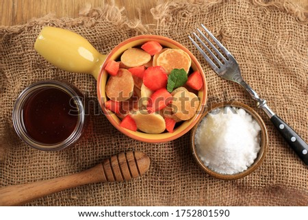 Close Up Yellow Bowl full of Tiny Pancake or Popular as Cereal Pancake, Popular Viral Snack During Quarantine in 2020. Served Above Jute Brown Background, Horizontal  version Picture