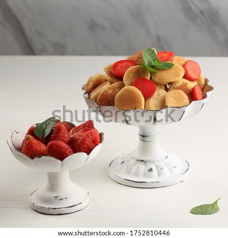 Cake Stand  with Tiny Pancake Cereal and Strawberries, Garnished with Mint Leaves and Lemon Slice on a White Background. Trendy food. Mini cereal pancakes. Square Picture with Marble Background