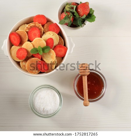Bowl with Tiny Pancake Cereal with Strawberries and Mint Leaves on a White Wooden Background. Trendy food. Mini cereal pancakes. Square Picture, Top View