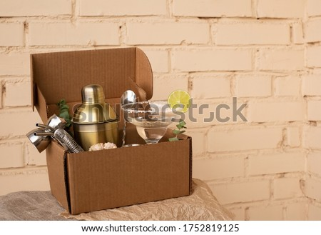 Stay at home bar cocktail party. Classic Margarita cocktail and bartender stuff parcel in a brown craft cardboard box. Gift to mixology lover. Beige brick wall background. Tender retro hipster colors. #1752819125