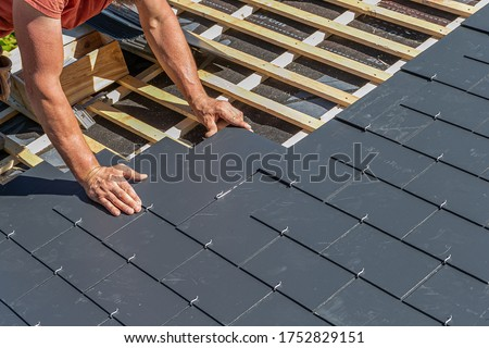Craftsman is installing a slate roof. Professional roof workers installing roof for a old house .Working on rooftop.  Royalty-Free Stock Photo #1752829151