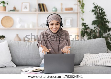 Teleconference. Smiling muslim woman having video call on laptop, talking with co-workers, gesturing at camera while sitting on couch in living room Royalty-Free Stock Photo #1753024541