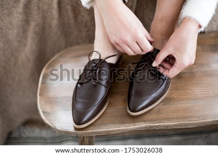 fashionable women's shoes, feet in the interior, classic women's flat shoes, brown leather shoes, mules and loafers, knitted blankets and blankets on the background, wooden background, cotton flowers, #1753026038