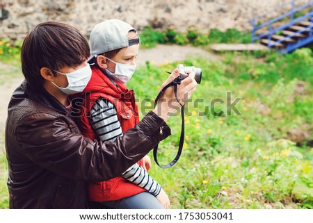 Son and dad spending time together outdoors. Father teaching his son to take pictures. Family trip to old castle. Coronavirus quarantine. Parents with son wearing face masks. Happy Father's day.