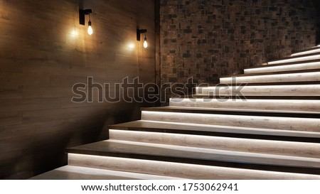 Illuminated staircase with wooden steps and illuminated at night in the interior of a large house #1753062941